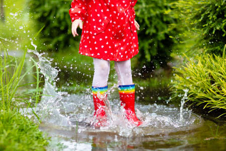 Kid playing in the rain in autumn park. Child jumping in muddy puddle on rainy fall day. Little girl in rain boots and red jacket outdoors in heavy shower. Kids waterproof footwear and coat.