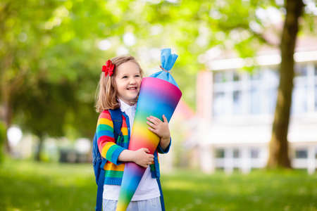 Happy child holding traditional German candy cone on the first school day. Little student with backpack and books excited to be back to school. Beginning of class in Germany with sweets for kids. Reklamní fotografie