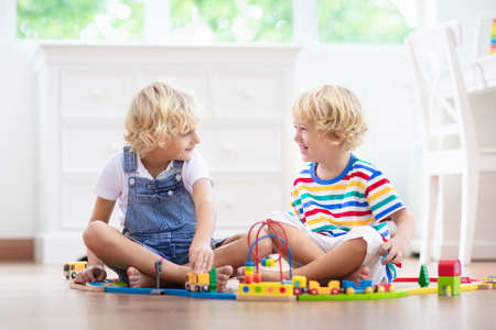 Kids play with wooden railway. Child with toy train. Educational toys for young children. Little boy building railroad tracks on white floor at home or kindergarten. Cute kid playing cars and engine. 免版税图像