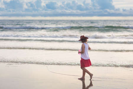 Child playing on tropical beach. Little girl wearing cowboy hat at sea. Family summer vacation. Kid searching for shells. Water and sand fun for children. Kids play on ocean coast Reklamní fotografie