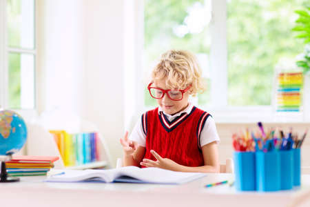 Kids go back to school. Children study and learn for preschool. Little boy of elementary class doing homework. Bedroom with desk, books and globe for young child. Kid learning to read and write.