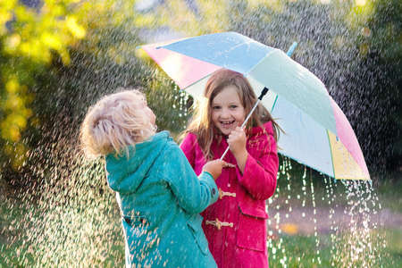 Kids with colorful umbrella playing in autumn shower rain. Little boy and girl in warm duffle coat play in a park by rainy weather. Fall outdoor fun for children. Kid catching rain drops. Stok Fotoğraf