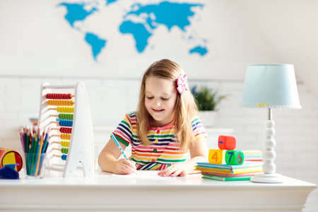 Child doing homework at home. Little girl with wooden colorful abacus doing math exercise learning addition and counting. Kids study and learn. Preschooler kid writing and reading. Back to school.