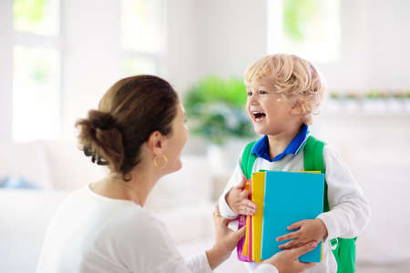 Child going back to school. Mother and kid getting ready for first school day after vacation. Little boy and mom going to kindergarten or preschool. Student packing books, apple and lunch in backpack. Reklamní fotografie