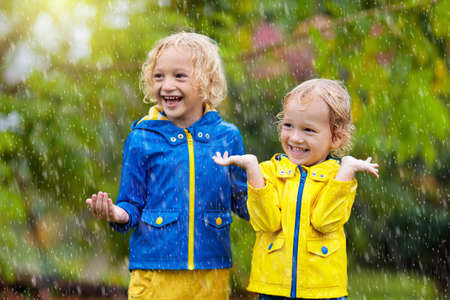 Kids play in autumn rain. Child playing outdoor on rainy day. Little boy catching rain drops under heavy shower. Fall storm in a park. Waterproof wear for kid. Children outdoors by any weather.