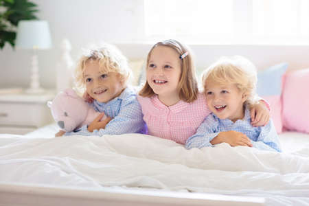 Kids play in bed. Children at home in white sunny bedroom. Brother and sister in matching pajamas playing in parents bedroom. Family morning. Boy and girl wake up or go to sleep.