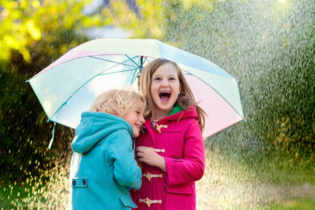 Kids with colorful umbrella playing in autumn shower rain. Little boy and girl in warm duffle coat play in a park by rainy weather. Fall outdoor fun for children. Kid catching rain drops. Reklamní fotografie