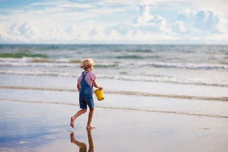 Child playing on tropical beach. Little boy with bucket sea. Family summer vacation. Water and sand fun for children. Kids play, run on ocean coast