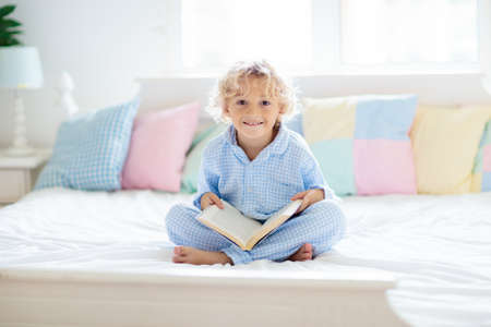 Child reading book in bed in white sunny bedroom with window. Children read books. Kids room. Little blond curly boy in pajamas at home. Bedding and sleepwear for nursery. Kid with toy.