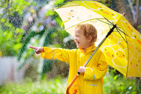 Child playing in the rain on sunny autumn day. Kid under heavy shower with yellow duck umbrella. Little boy with duckling waterproof shoes. Rubber wellies boots. Fall outdoor activity by rainy weather Stok Fotoğraf