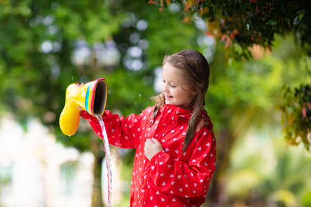 Kid with rubber boots playing in the rain in autumn park. Child in muddy puddle on rainy fall day. Rain boot full of water. Little girl in red jacket outdoors in heavy shower. Kids waterproof footwear
