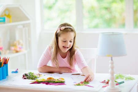 Kind, das Bild mit bunten Blättern erstellt. Kunst und Basteln für Kinder. Kleines Mädchen, das Collagenbild mit Regenbogenpflanzenblatt macht. Biologiehausaufgaben für junge Schüler. Kreativer Herbstspaß zu Hause.