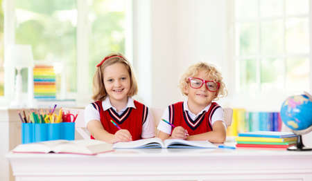 Kids go back to school. Children study and learn for preschool. Boy and girl of elementary class doing homework. Bedroom with desk, books and globe for young child. Kid learning to read and write. Reklamní fotografie