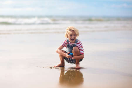 Child playing on tropical beach. Little boy with toy car. Family summer vacation. Water and sand fun for children. Kids play, run on ocean coast
