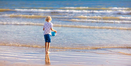 Child playing on tropical beach. Little boy with bucket and spade at seashore. Family summer vacation. Kid building sandcastle. Kids search for shells and play. Water and sand fun for children.