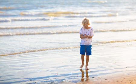 Child playing on tropical beach. Little boy at seashore. Family summer vacation. Kid building sandcastle. Kids search for shells and play. Water and sand fun for children. Reklamní fotografie