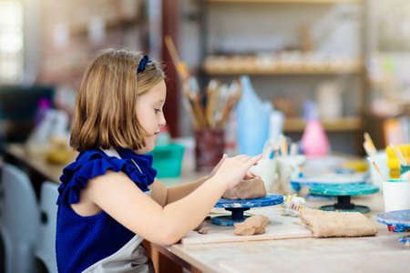 Child working on pottery wheel  Kids arts and crafts class in