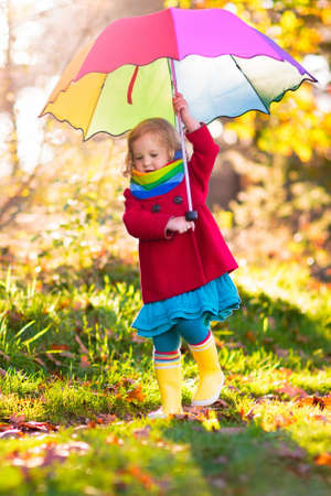 Kid playing out in the rain. Children with umbrella and rain boots play outdoors in heavy autumn rain. Little girl jumping in muddy puddle. Kids fun by rainy fall weather. Child running in storm. Stockfoto