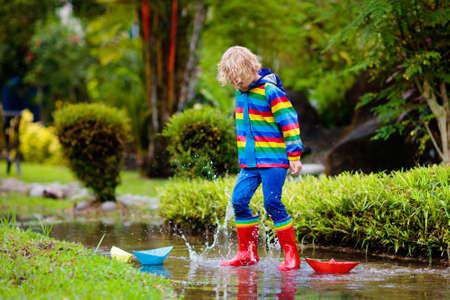 Bambino che gioca con la barchetta di carta nella pozzanghera. I bambini giocano all'aperto sotto la pioggia autunnale. Attività all'aperto con tempo piovoso autunnale per bambini piccoli. Bambino che salta nelle pozzanghere fangose. Giacca e stivali impermeabili per bambino.
