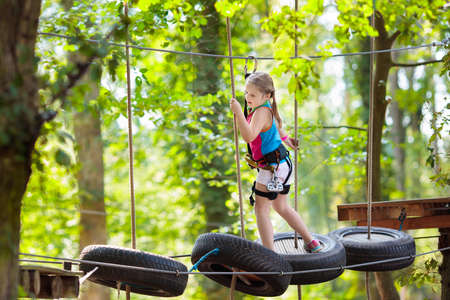 Child in forest adventure park. Kids climb on high rope trail. Agility and climbing outdoor amusement center for children. Little girl playing outdoors. School yard playground with rope way.