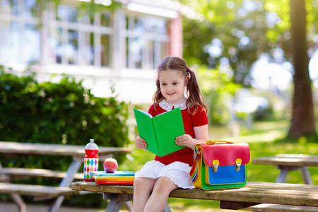 Kind geht zurück zur Schule. Beginn des neuen Schuljahres nach den Sommerferien. Kleines Mädchen mit Rucksack und Büchern am ersten Schultag. Beginn des Unterrichts. Bildung für Kindergarten- und Vorschulkinder.
