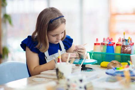 Kind, das an der Töpferscheibe arbeitet. Kinder-Kunsthandwerk-Klasse in der Werkstatt. Kleines Mädchen, das eine Tasse und eine Schüssel mit Ton herstellt. Kreative Aktivität für kleine Kinder in der Schule. Nettes Kind, das Spielzeug mit Keramik bildet.
