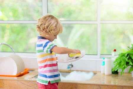 Child washing dishes. Home chores. Kid in white kitchen cleaning plates after lunch at window. Banco de Imagens - 128867133