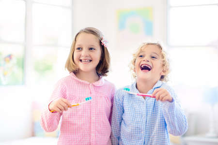 Child brushing teeth. Kids with toothpaste and brush. Dental and oral hygiene, care. Healthy daily routine for children. Kid after shower or bath at home. Girl and boy in pajamas with tooth paste. Stok Fotoğraf