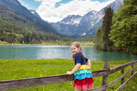 Child hiking in the Alps mountains looking at beautiful lake. Kid in alpine flower field at snow covered mountain in Austria. Spring family vacation. Little girl on scenic hike trail. Outdoor fun.