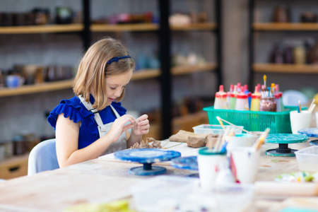 Child working on pottery wheel. Kids arts and crafts class in workshop. Little girl creating cup and bowl of clay. Creative activity for young children in school. Cute kid forming toy with ceramic.