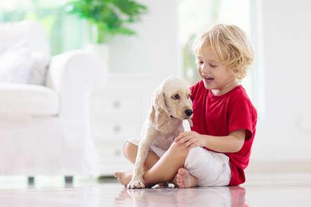 Niño jugando con perro bebé. Los niños juegan con el cachorro. Niño y cocker spaniel americano en el sofá en casa. Niños y mascotas en casa. Niño sentado en el suelo con mascota. Cuidado animal.