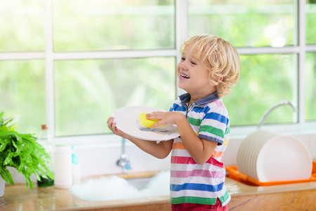 Niño lavando platos. Tareas del hogar. Cabrito en platos de limpieza de cocina blanca después del almuerzo en la ventana. Foto de archivo