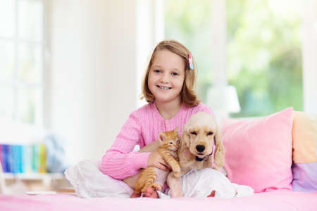 Child playing with baby dog and cat. Kids play with puppy and kitten. Little girl and American cocker spaniel on bed at home. Children and pets at home. Kid taking nap with pet. Animal care.