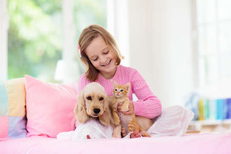 Child playing with baby dog and cat. Kids play with puppy and kitten. Little girl and American cocker spaniel on bed at home. Children and pets at home. Kid taking nap with pet. Animal care. Banco de Imagens - 129423546
