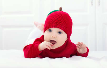 Baby in knitted apple hat. Kid on white bed. Child wearing red autumn sweater at home. Halloween or fall season costume. Фото со стока