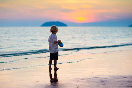 Child playing on ocean beach. Kid jumping in the waves at sunset. Sea vacation for family. Little boy running on exotic island during summer holiday. Banco de Imagens