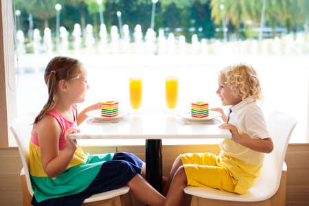 Kids eat rainbow cake at restaurant. Boy and girl with sweets and pastry. Children drinking fresh orange juice in cafe. Family eating out in city cafeteria. Birthday party. Healthy food for young kid.