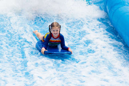 Little girl surfing in beach wave simulator attraction in water amusement park of tropical resort. Child trying to ride body board. Kids surf. Preschooler kid surfer during training on generated waves