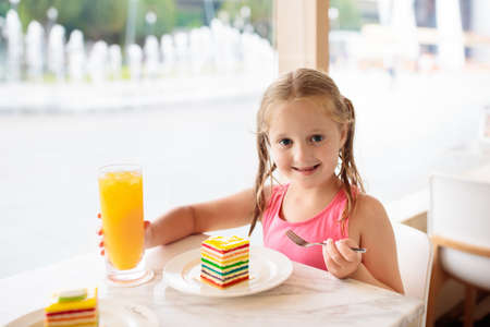 Kids eat rainbow cake at restaurant. Little girl with sweets and pastry. Child drinking fresh orange juice in cafe. Family eating out in city cafeteria. Birthday party. Healthy food for young kid.