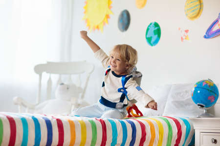 Kids play astronaut. Little boy in space costume jumping on bed with rocket. Solar system and planet room decoration. Creative child, future profession. Фото со стока