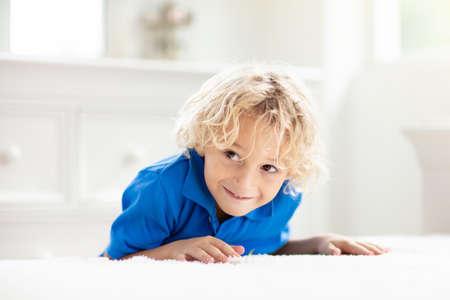 Kind speelt verstoppertje. Kleine jongen op wit bed. Kinderen thuis. Stockfoto