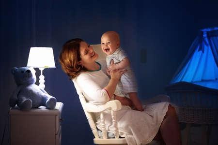 Madre y bebé leyendo un libro en el dormitorio oscuro. Mamá e hijo leen libros antes de acostarse. Familia en la noche. Interior de sala infantil con lámpara de noche y moisés. Padre con bebé junto a la cuna.