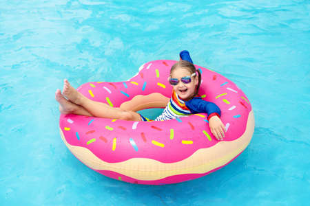 Child in swimming pool on funny inflatable donut float ring. Little girl learning to swim in outdoor pool of tropical resort. Water toys for kids. Healthy sport activity for children. Sun protection.
