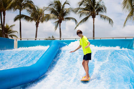 Teenager surfing in beach wave simulator attraction in water amusement park of tropical resort. Teen age boy trying to ride body board. Surf fun. Young surfer during training on generated waves