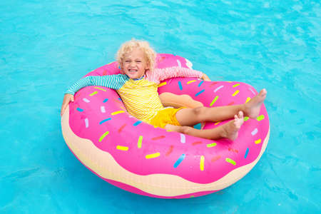 Child in swimming pool on funny inflatable donut float ring. Little boy learning to swim in outdoor pool of tropical resort. Water toys for kids. Healthy sport activity for children. Sun protection. Фото со стока