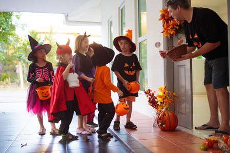 Dolcetto o scherzetto per bambini nella notte di Halloween. Bambini asiatici e caucasici di razza mista alla porta di casa decorata. Ragazzo e ragazza in costume da strega e vampiro e cappello con secchio di caramelle e lanterna di zucca.