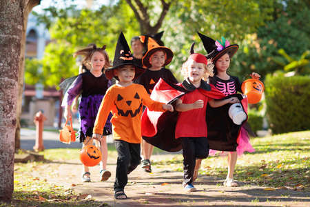 Child in Halloween costume. Mixed race Asian and Caucasian kids and parents trick or treat on street. Little boy and girl with pumpkin lantern and candy bucket. Baby in witch hat. Autumn holiday fun. Archivio Fotografico - 129676061