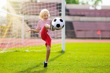 Kids play football on outdoor stadium field. Children score a goal during soccer game. Little boy kicking ball. School sports club. Training for young player.