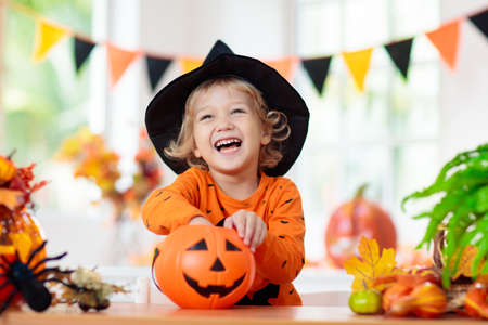 Child in Halloween costume. Kids trick or treat. Little boy with pumpkin lantern. Baby in witch hat. Autumn season holiday decoration. Home festive interior with fall leaves and squash.