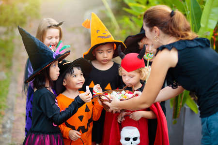 Kids trick or treat on Halloween night. Mixed race Asian and Caucasian children at decorated house door. Boy and girl in witch and vampire costume and hat with candy bucket and pumpkin lantern. Stock fotó